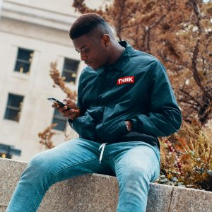 Man looking at phone, sitting, outside