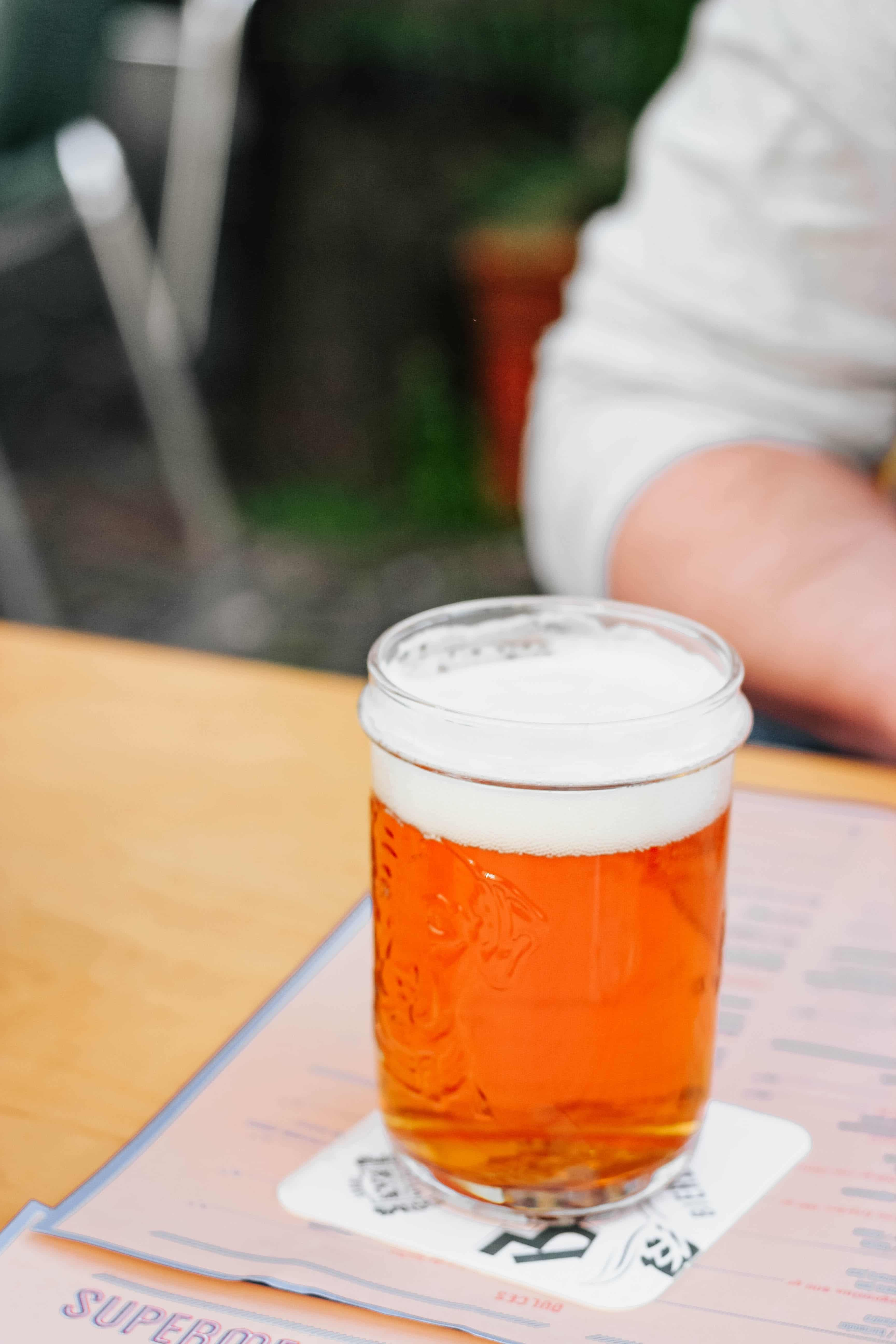 Glass of beer on a table. Photo by Micheile Henderson on Unsplash.